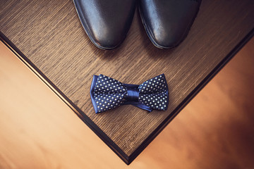 A pair of black leather shoes stand on a dark table next to a bow tie