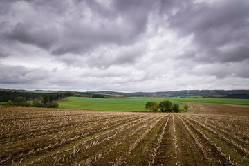 Dark clouds above harvested cronfield typical landscape Belgium Ardennes