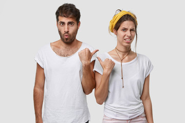 Unhappy young woman with European appearance, points with thumb at surprised guy, express dislike and surprisement, wear casual t shirts, isolated over white studio background. Just look at him!