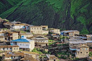 Village against dark mountain