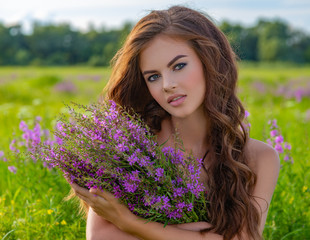 Young woman outdoors with a bouquet.
