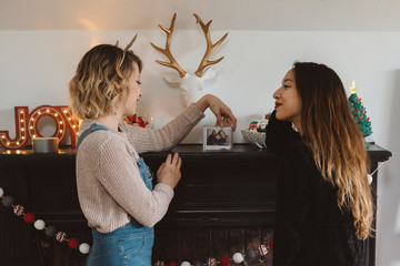 Two female roomates decorating their apartment for christmas