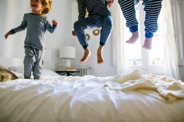 Kids wearing pajama jumping on bed.