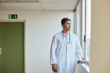 Portrait of standing doctor looking out through the window in a hospital