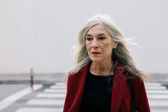 Mature woman with grey long hair crossing the street.