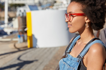Sideways outdoor shot of pleased black young woman with Afro hairstyle, wears glasses, denim overalls, focused into distance, has walk in open air during summer vacation, strolls in unknown city