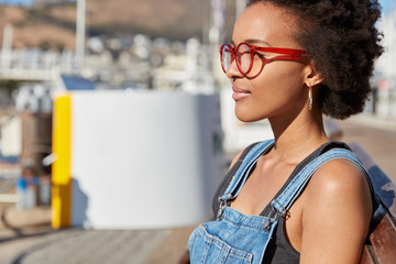 Shot of stylish teenage girl with Afro haircut, wears optical glasses for good vision, dressed in denim overalls, models against blurred city background, thinks about new traveling. Leisure concept