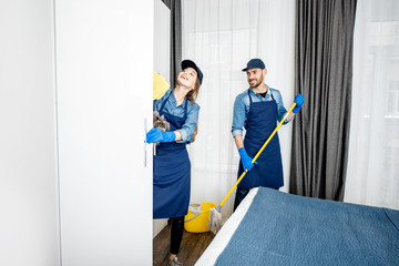 Professional cleaners in blue uniform washing floor and wiping furniture in the white hotel room or apartment bedroom. Cleaning service concept