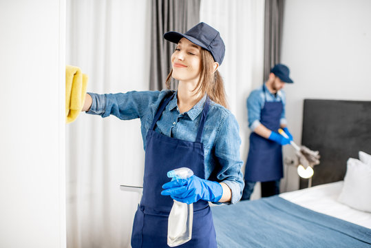 Couple as a professional cleaners in uniform rubbing furniture and wiping dust in the bedroom or hotel room. Cleaning service concept