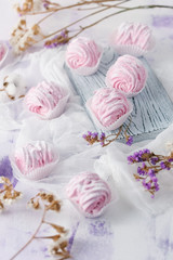 fruit marshmallow homemade on a soft pink background and dried flowers
