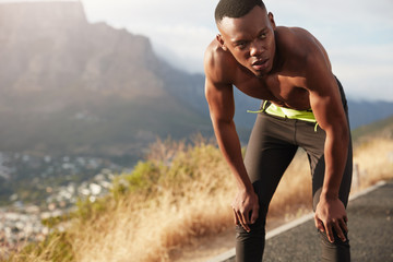 Healthy black male adult has workout at mountain road, trains for marathon, keeps both hands on knees, looks thoughtfully into distance, runs in countryside, has determined facial expression.