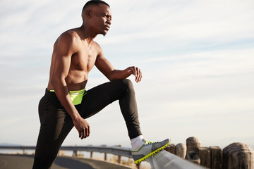 Exhausted black male runner rests after active run, wears sneakers, poses against white sky background, thinks about future sport competitions, has hard sport workout. Jogging and motivation