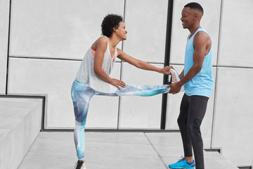 Horizontal view of fit female stretches legs, warms up before race competitons, boyfriend helps her, keeps leg, controls balance, wear sportclothes, look happily at each other. Sport concept