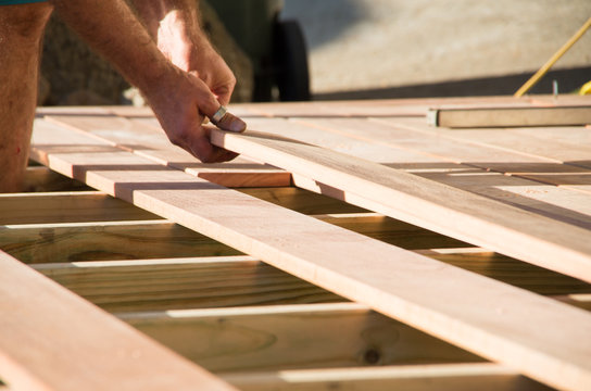 Man placing a plank of wood in a deck home renovation