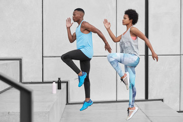 Motivated active ethnic couple run up stairs together, jump highly, train climbing staircase in...