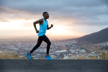 Full length horizontal shot of fast male runner enjoys speed, photographed in motion, runs along road with mountain and city view in background. Running at dawn concept. Strong sportsman outside