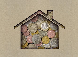 Coins under a sheet of paper with a carved house