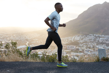 Outdoor shot of active dark skinned man joggs at morning, has regular trainings, dressed in tracksuit and comfortable sneakers, concentrated into distance, sees finish far away. Rock in background