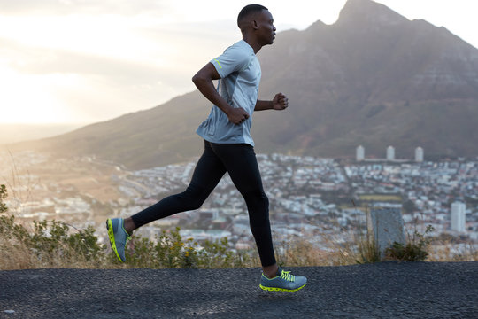 Sideways shot of handsome active man runs against mountain beautiful scenery, photographed in motion, enjoys workout, being very fast and energetic, wears sportclothes. Athlete black male outside