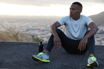 Carefree pensive black man leans hands on knees, rests on asphalt, drinks fresh water, breathes air, enjoys loneliness, models over panoramic blurred view with copy space for your advertising