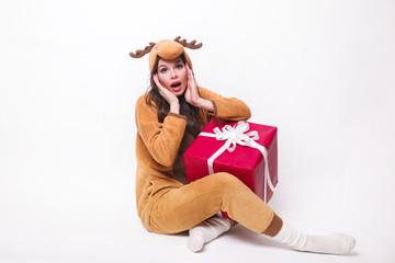 8fbc9d63fda3 Kigurumi pajamas deer. Cute young woman in pajamas sitting with big red  present box and