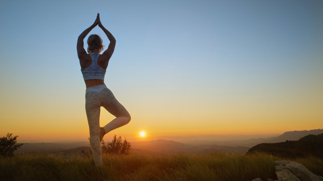 AERIAL: Flexible Caucasian woman holds a scorpion pose in front of the sunrise.