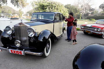 A visitor with children takes a picture of a vintage car before the start of the 9th annual cross-country rally, organised by the VCCCP at the premises of the Governor House in Karachi