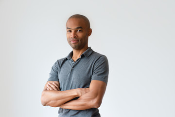 Successful bald African American man standing with crossed arms. Confident smiling man posing in gray t-shirt. Success concept Wall mural