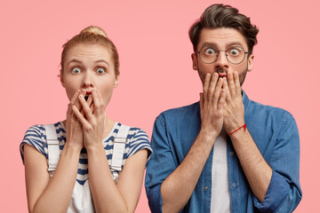 Horizontal view of stupefied young woman and man cover mouthes with fear, have surprised facial expressions, find out tragic news from speaker, stand shoulder to shoulder against pink background