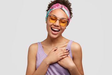Beautiful positive friendly looking female keeps both hands on chest, express gratitude to sister for help and advice, wears fashionale shades and sunglasses, isolated over white wall. Thankfulness