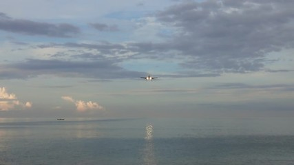 Wall Mural - Passenger airplane before landing over tropical beach at morning