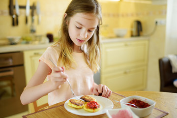 Cute little girl enjoying her breakfast at home. Pretty child eating pancakes with strawberry sauce before school.