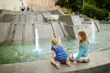 Two cute little girls playing by city fountain on hot and sunny summer day. Children having fun with water in summer.