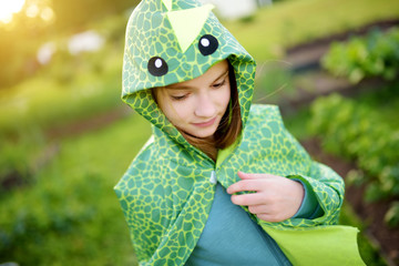 Funny little girl dressed as a dragon having fun outdoors on summer day.