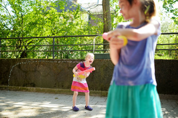 Adorable little girls playing with water guns on hot summer day. Cute children having fun with water outdoors.