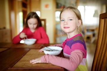 Two cute little sisters eating a soup in cozy dining room. Children having a dinner at home.