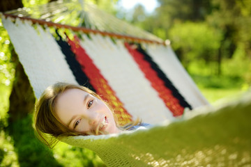 Happy little girl relaxing in hammock on beautiful summer day. Cute child having fun in spring garden.