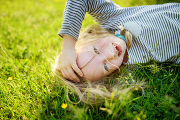 Cute little girl having fun on a grass on the backyard on sunny summer evening.