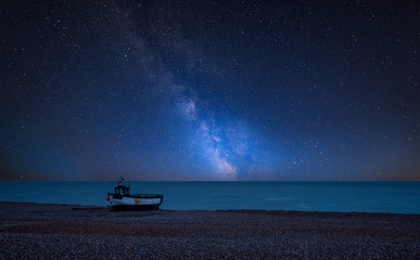 Vibrant Milky Way composite image over landscape of Abandoned derelict fishing boats on shingle beach