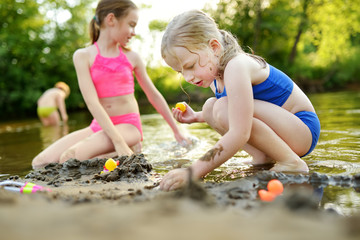 Two little sisters having fun on a sandy lake beach on warm and sunny summer day. Kids playing by the river.