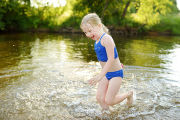 Cute little girl having fun on a sandy lake beach on warm and sunny summer day. Kid playing by the river.