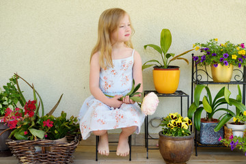Cute little girl sitting by flower pots on sunny summer evening.
