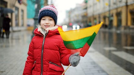 Cute little girl celebrating Lithuanian Independence Day holding tricolor Lithuanian flag in Vilnius