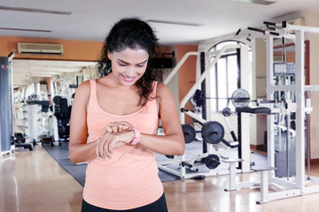 Beautiful woman with smartwatch in the gym center