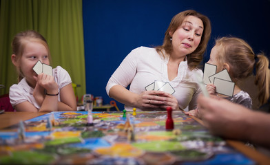 Board game concept. The family is having fun playing together at home in a board game. Board game field, many figures, coins and sandglass. Four people play, holding cards joyful emotions on the face.