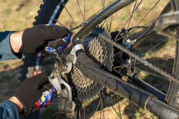 Bike repair. Cyclist repairing bicycle outdoors, close-up.