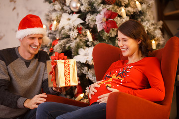 Picture of happy man in Santa cap with gift and pregnant woman on background of decorated Christmas tree