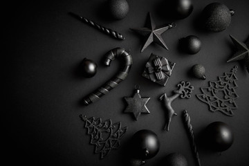 Christmas minimalistic and simple composition in mat black color. Christmas gifts, decorations on black background. Flat lay, top view with copy space