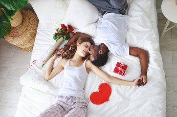 Valentine's Day. happy couple  with flowers in bed.