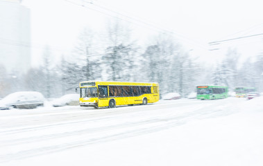 Yellow city bus rides a snowbound road during a snow storm. Abstract blur background. Concept of dangerous road conditions in winter